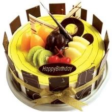 圓形鮮奶水果蛋糕,黃綠色果漿鋪面,時令水果,巧克力片裝飾,巧克力片圍邊。