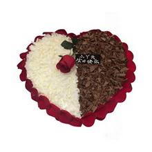 心形巧克力蛋糕,上層一支紅色新鮮玫瑰花,左右兩邊分別白色、黑色巧克力屑鋪面,新鮮玫瑰花瓣外圍