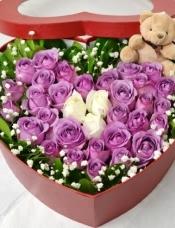 中间白玫瑰3支,外围精品紫玫瑰33支,绿材+满天星围绕,小公仔一只