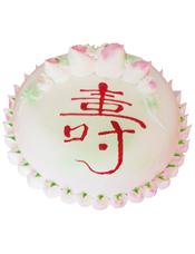 圆形鲜奶蛋糕,大小不同的蟠桃,蛋糕上写一个大红色的寿字