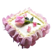 方形鲜奶蛋糕,上面一支新鲜的玫瑰花装饰,侧面新鲜的玫瑰花瓣外围
