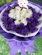 11枝白玫瑰居中,小熊1只,周边围一圈紫色勿忘我。