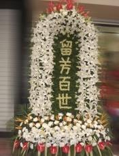 百合围成的拱形形状,中间用小簇菊拼成的留芳百世四个字,菊花和红掌点缀,散尾葵装饰。