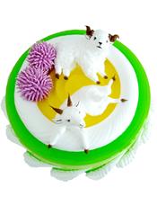圆形奶油蛋糕,两朵粉色奶油花,两只小羊装饰,绿色果酱围边。